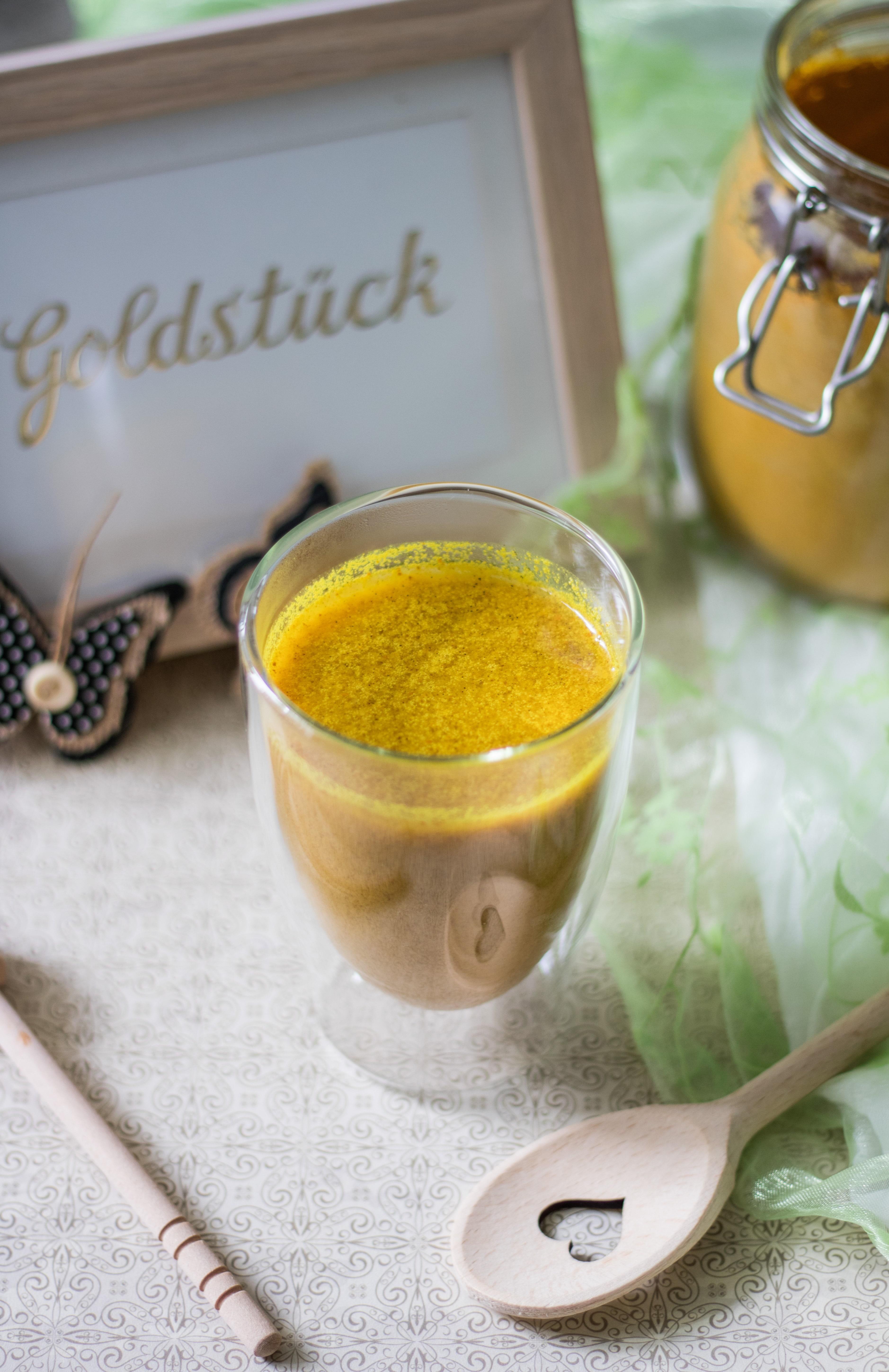 Goldene Milch mit Honiglöffel