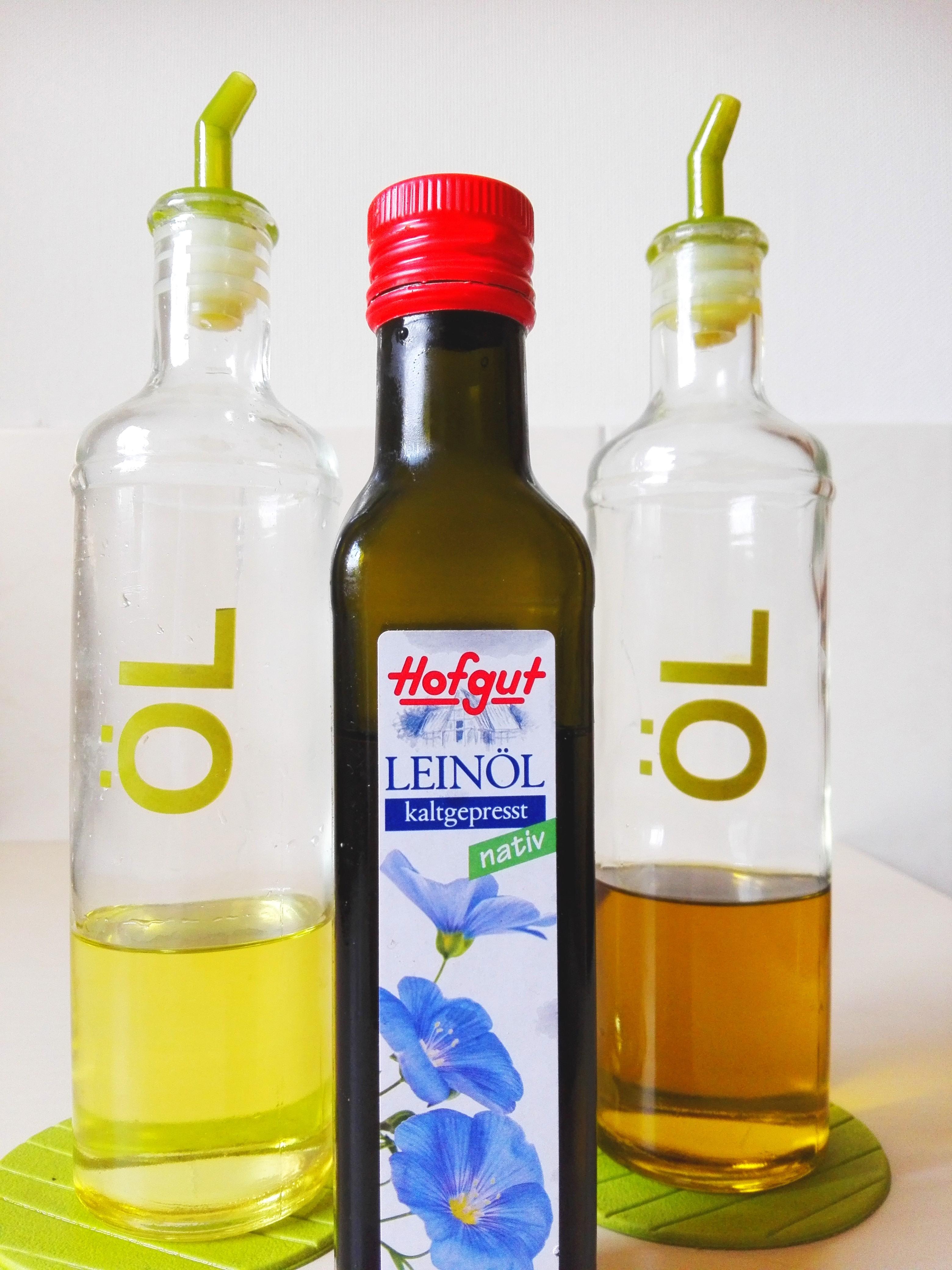 Speiseöle im Vergleich, Öle in einer Flasche , rechts: Sonnenblumenöl, links: Rapsöl, Mitte:Leinöl
