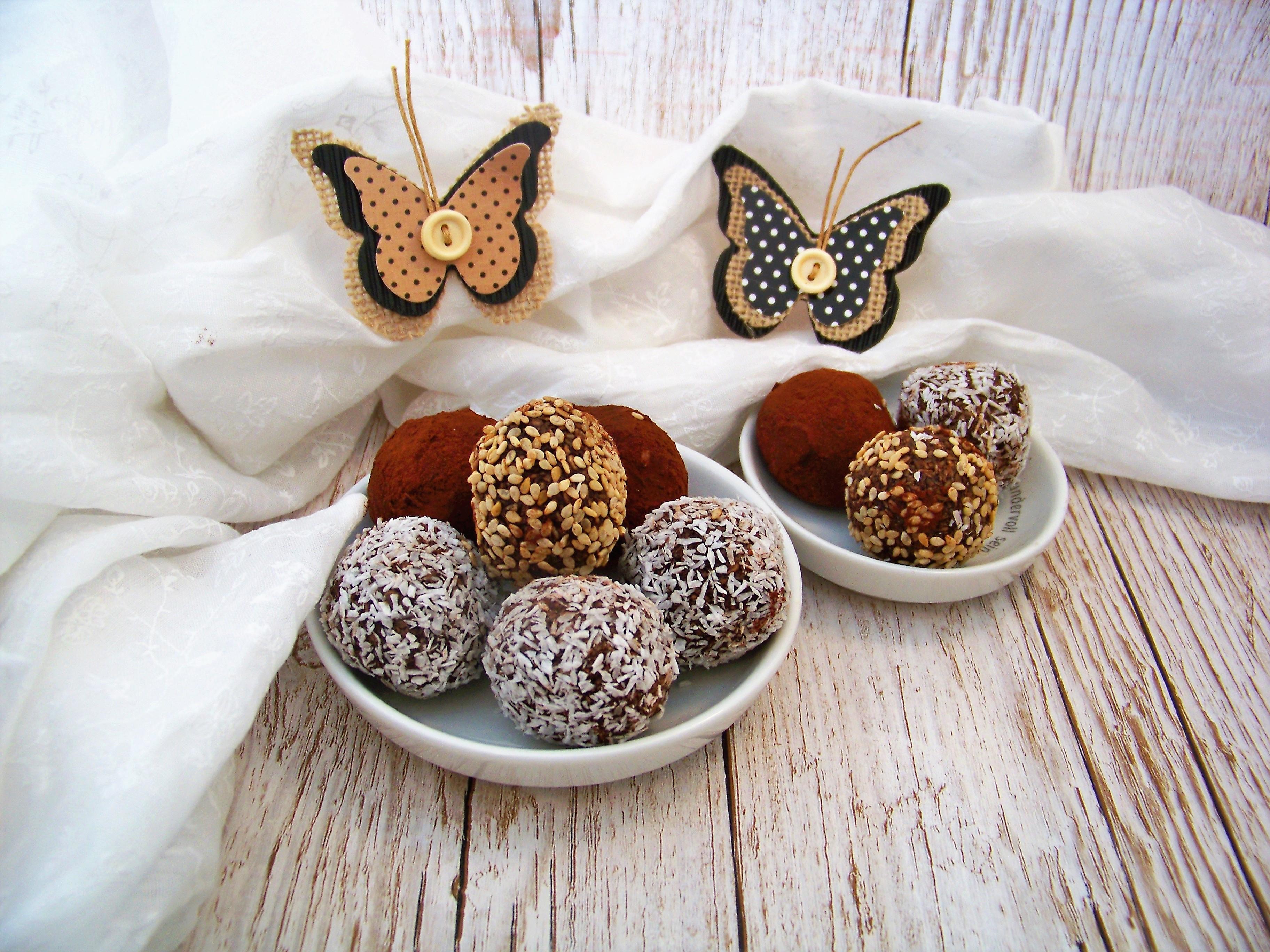 Energiekugeln mit Datteln, Kokos und Nussmus dekoriert auf kleinen Tellern