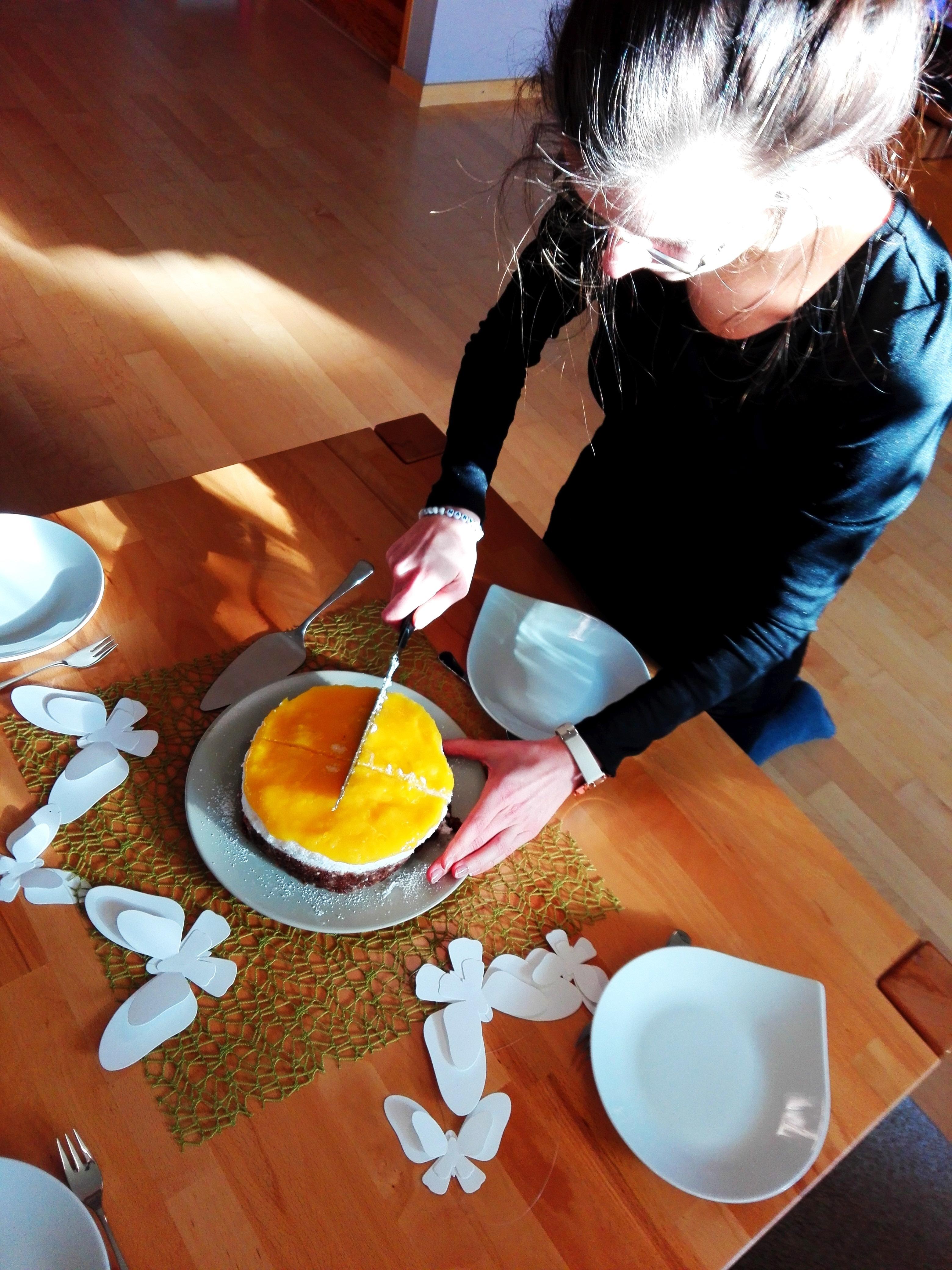 Kokos-Mango-Torte-vegan Kaja Neumann Ahafoods schneidet ihre Torte an