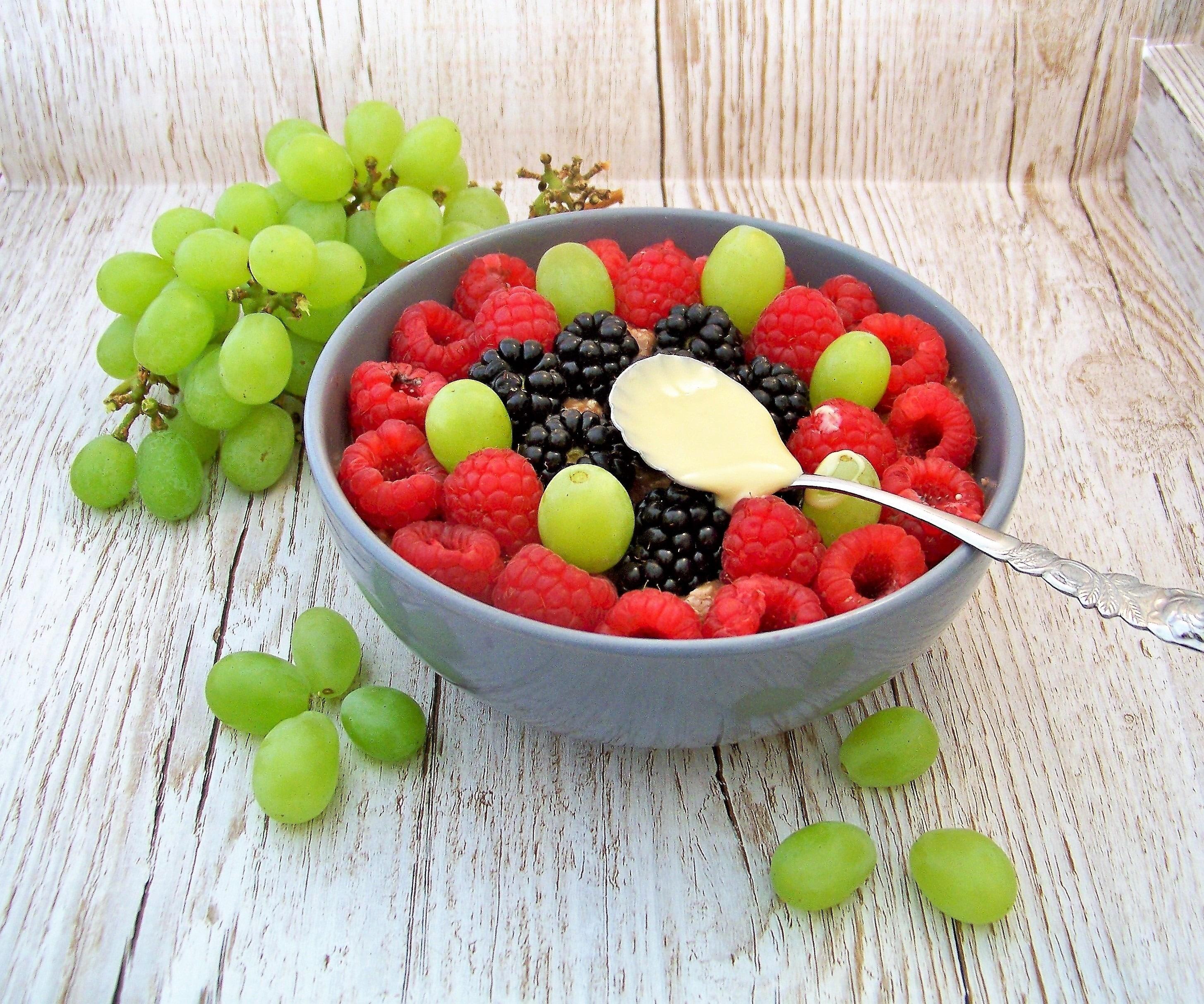 Overnight-Oats mit Beeren, Weintrauben und Mandelmus in einer grauen Schüssel