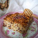 Frühstückskuchen-mit-Haferflocken-und-Leinsamen -Kuchenstück auf Teller mit Honiglöffel