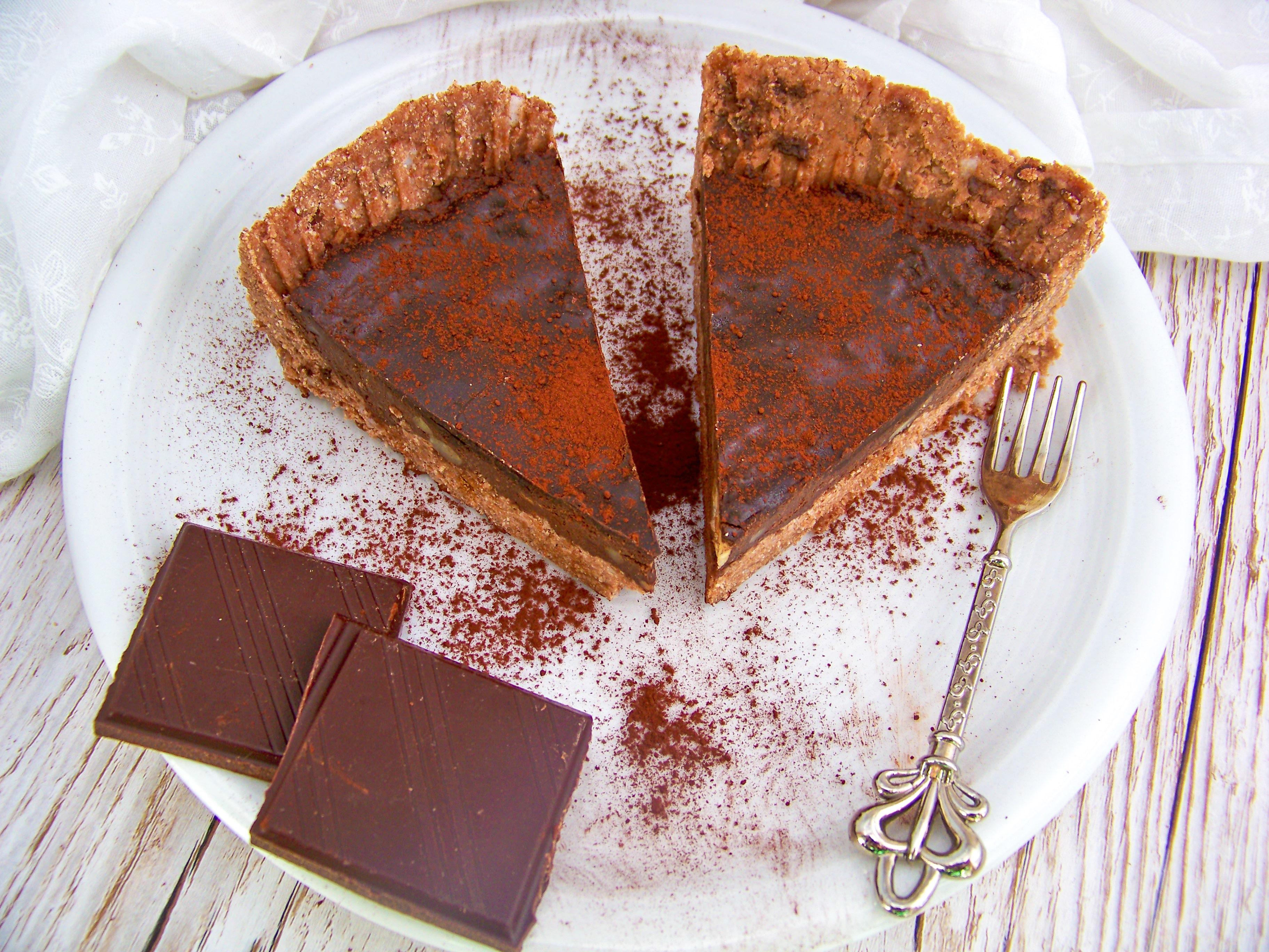 Roh vegane Schokotarte mit Kuchengabel und Schokolade