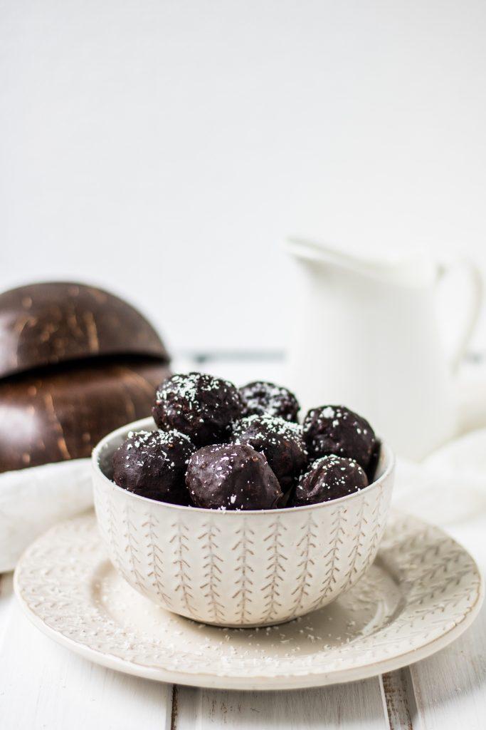 einfache vegane Schoko-Kokos-Kugeln  in weißer Schüssel in Schale mit Milchkännchen im Hintergrund