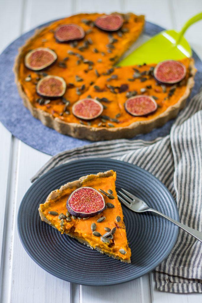 Glutenfreie und vegane Kürbis-Tarte. Tartestück auf Kuchenteller und Form in Hintergrund