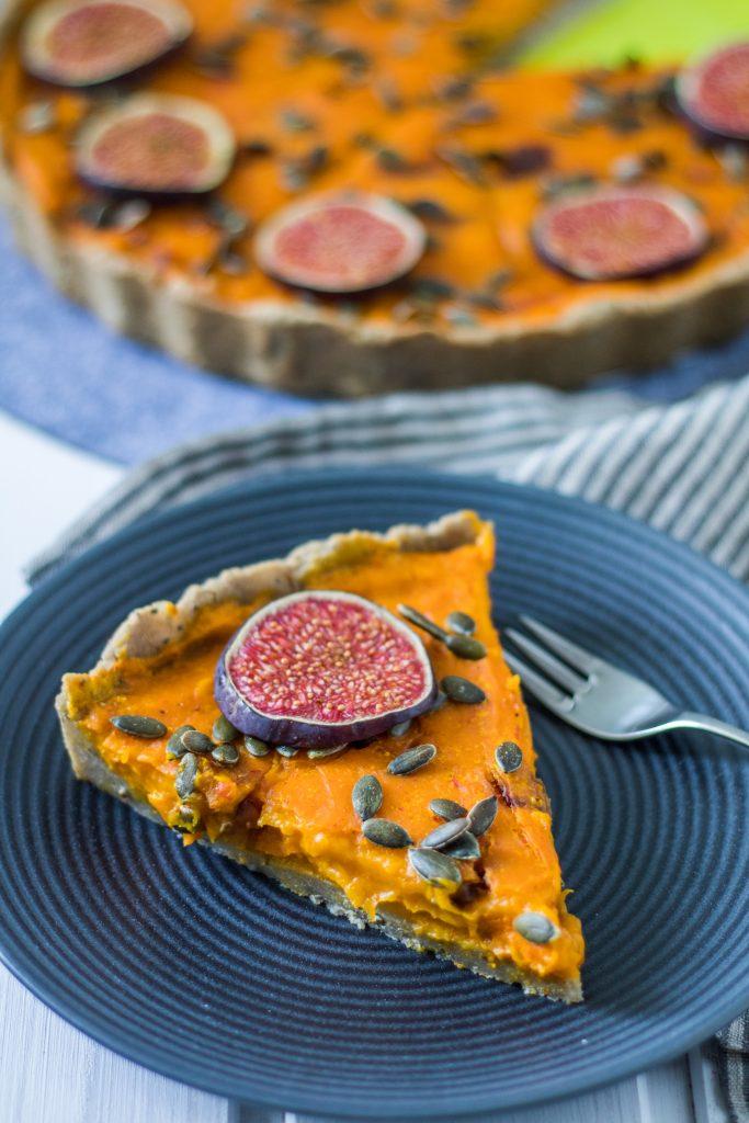 Glutenfreie und vegane Kürbis-Tarte. Tartestück auf Teller mit Gabel