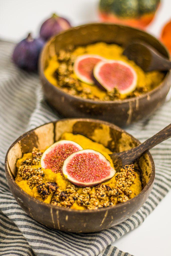 veganer cremiger Kürbis-Porridge mit Dattelsüße und Feigen und Sesamcrunch in Kokosnussschale