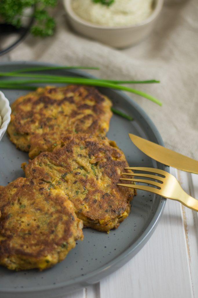 Knusprige vegane Mais-Bratlinge auf einem Teller mit goldenem Besteck