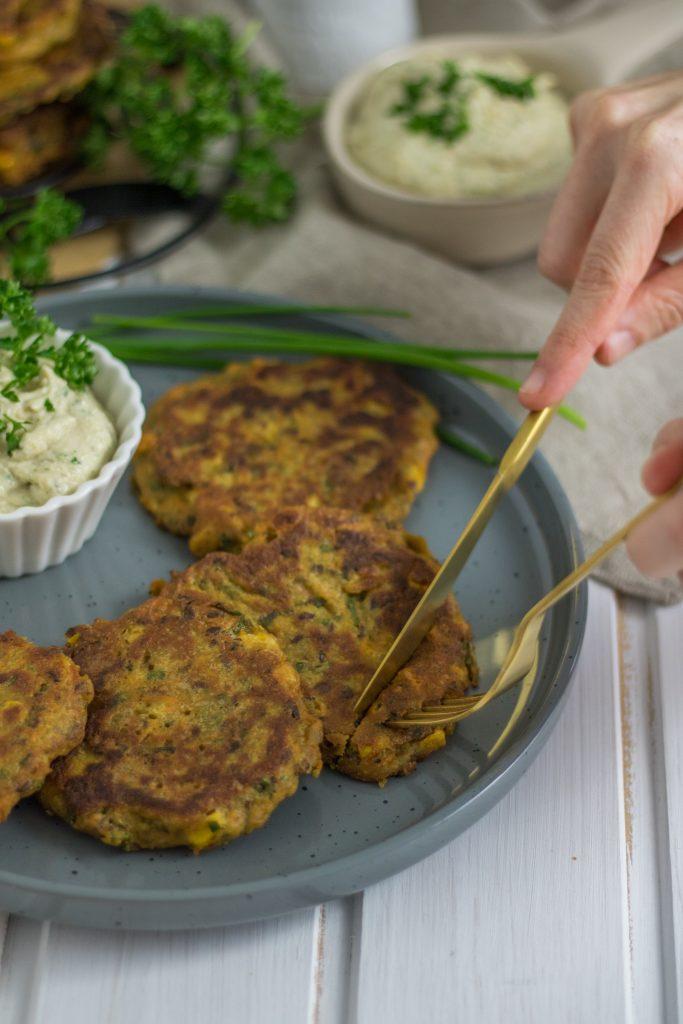 Knusprige vegane Mais-Bratlinge essen mit Messer und Gabel