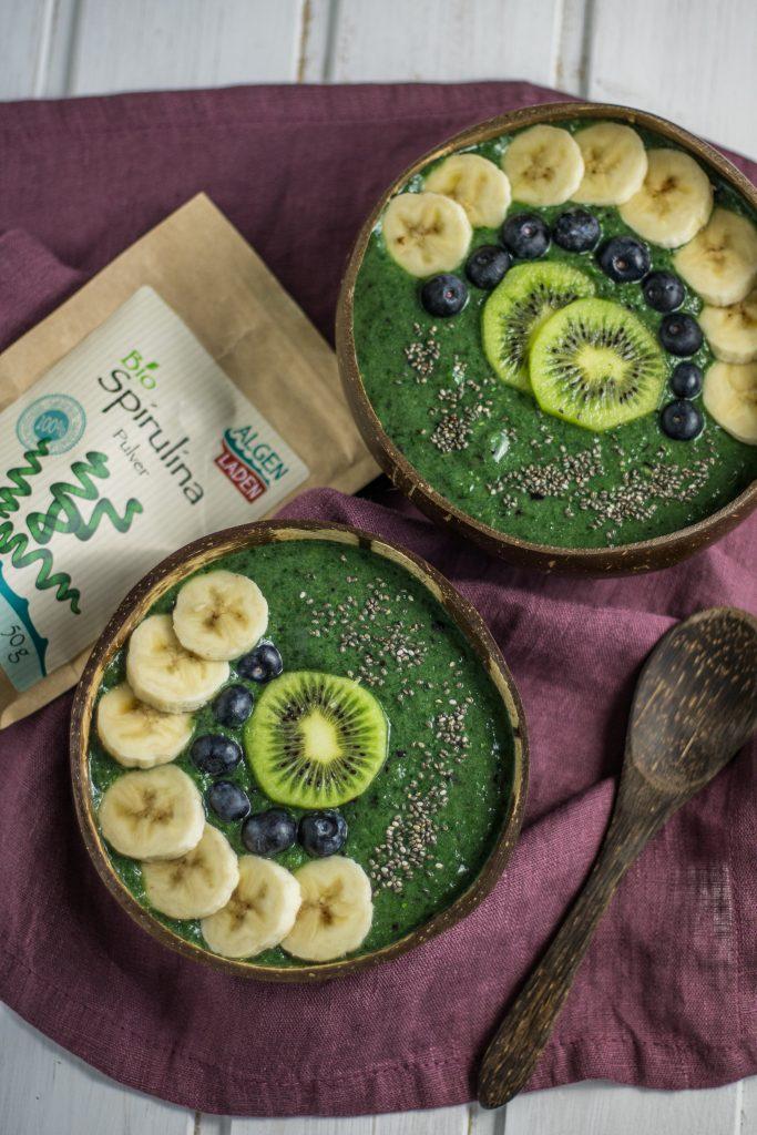 Smoothiebowl mit Spirulina und Chlorella mit Kiwi, Blaubeeren und Bananenscheiben und Spirulina Verpackung