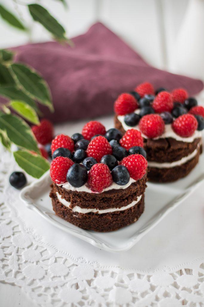 Vegane Schoko-Kokos-Törtchen mit Beeren auf Kuchenplatte