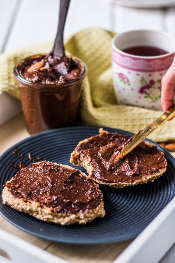 Vegane Nuss-Nougat-Creme selber machen.  Vegane Nutella auf Brötchen verstreichen