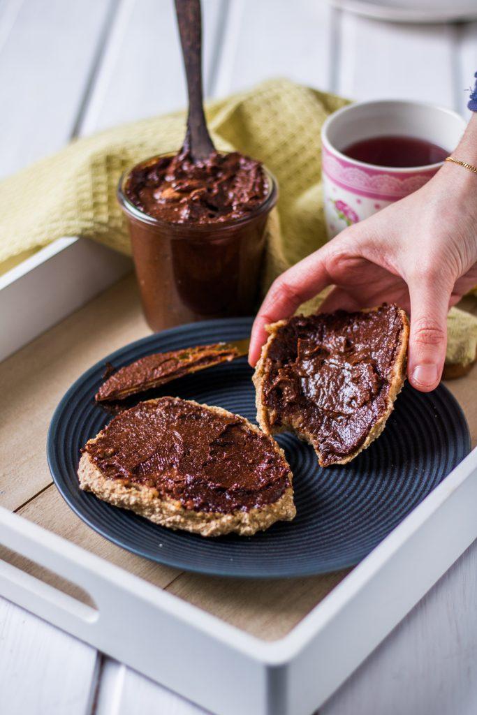 Vegane Nuss-Nougat-Creme selber machen Hand greift nach Brötchen