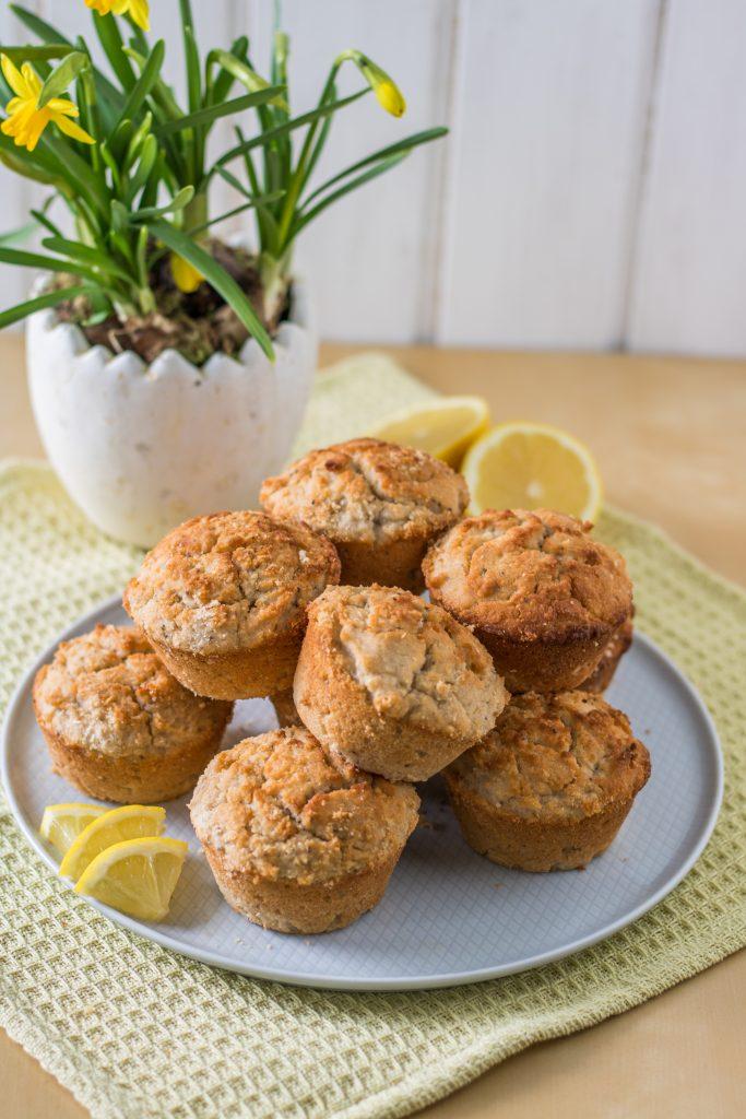 Glutenfreie und vegane Zitronen-Kokos-Muffins auf einer Kuchenplatte