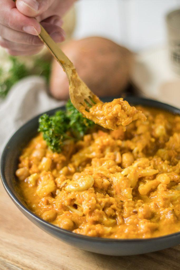 veganes Blumenkohl-Kichererbsen-Curry mit Süßkartoffel Nahaufnahme mit Gabel