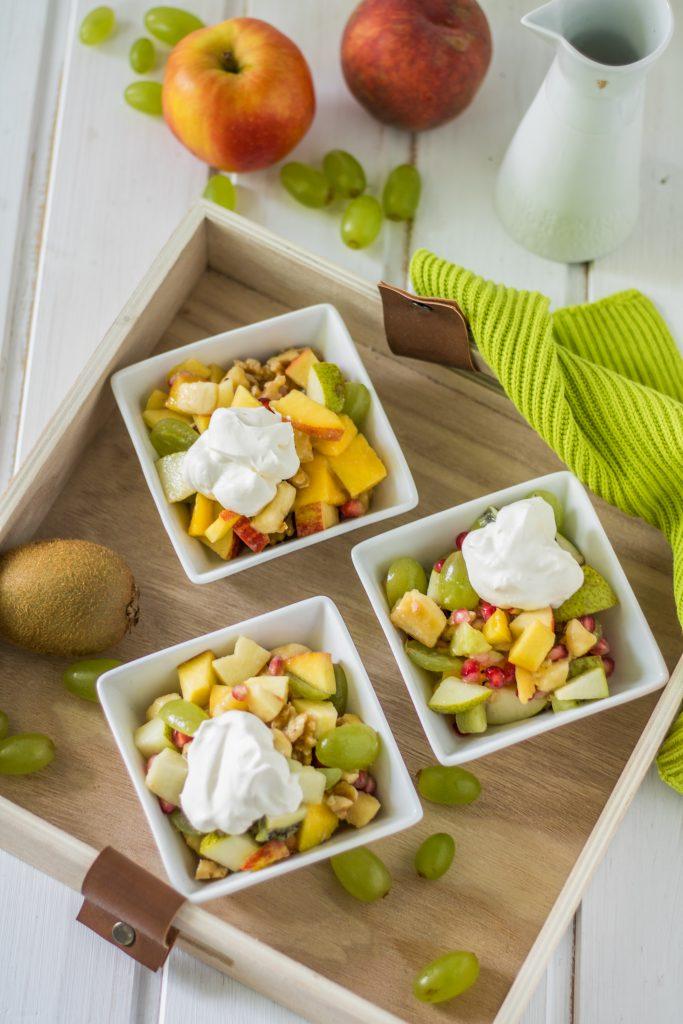Bunter Obstsalat mit Ahornsirup-Zitronensaft-Dressing und veganer Schlagsahne von oben