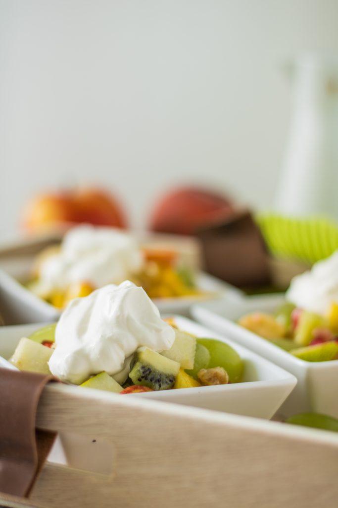 Bunter Obstsalat mit Ahornsirup-Zitronensaft-Dressing und veganer Schlagsahne von vorne