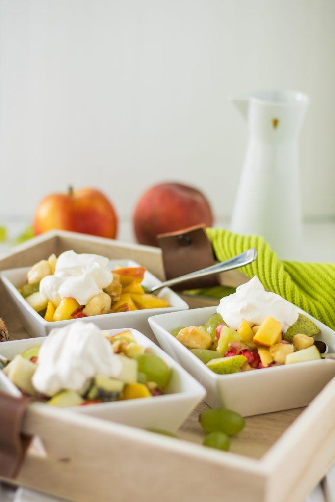 Bunter Obstsalat mit Ahornsirup-Zitronensaft-Dressing und veganer Schlagsahne auf Holztablett