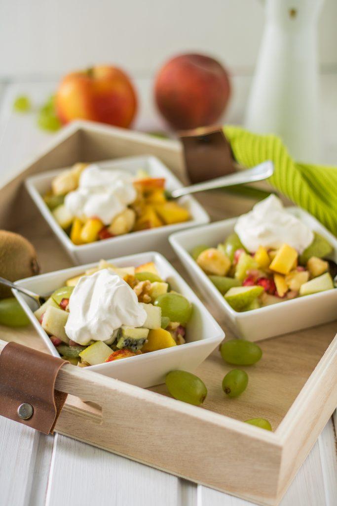 Bunter Obstsalat mit Ahornsirup-Zitronensaft-Dressing und veganer Schlagsahne in Schälchen